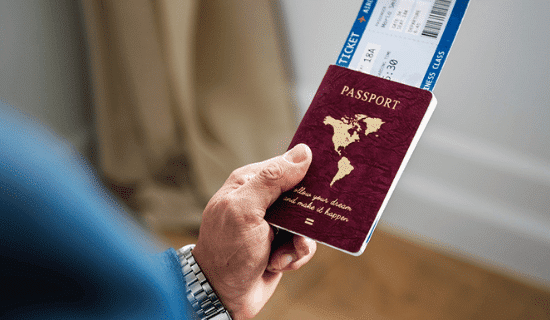 man carrying passport and plane ticket