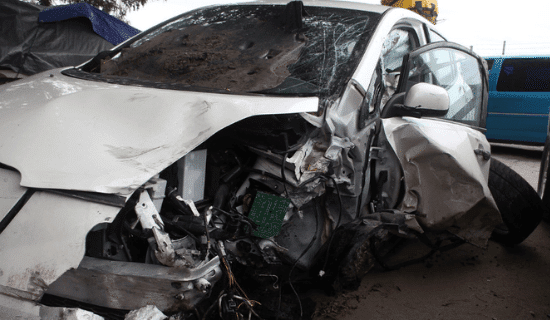 A car that has been damaged by a tractor trailer