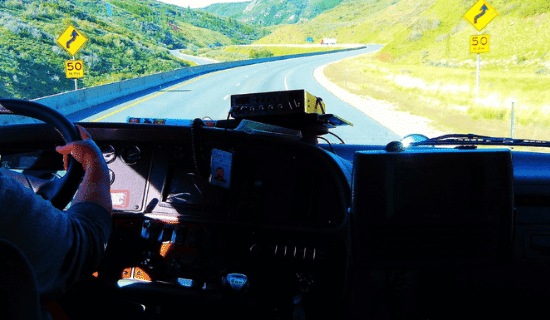 A man driving a semi truck through a hilly area