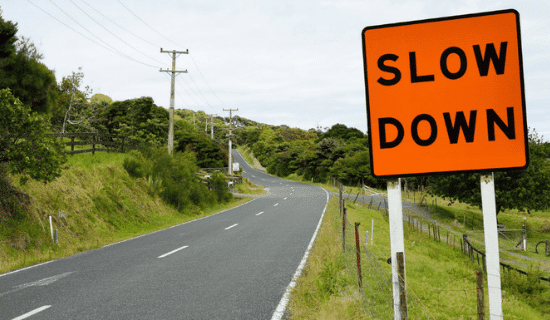 a road and a slow down sign