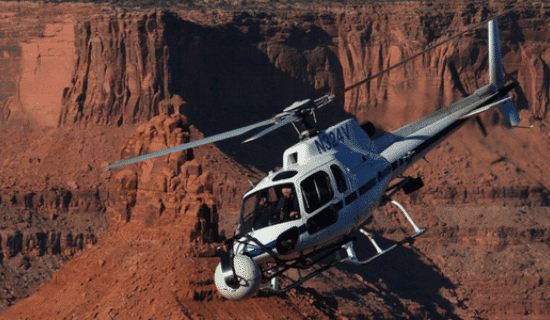 A white and black helicopter flying through the Grand Canyon