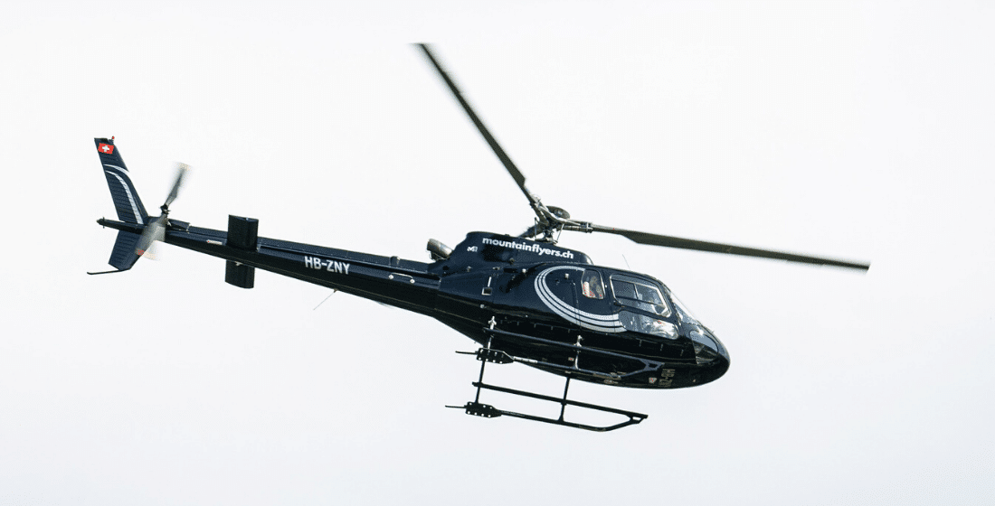 A black and white helicopter midflight