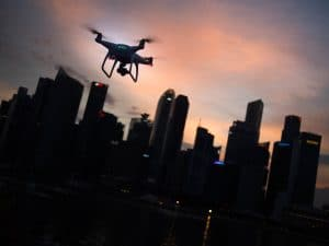 A drone flies at sunset over a city skyline.